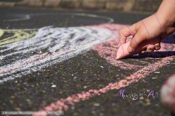 Kind malt mit Kreide auf Asphalt