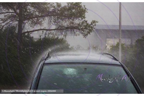 Starker Wolkenbruch mit Regen trifft ein Auto