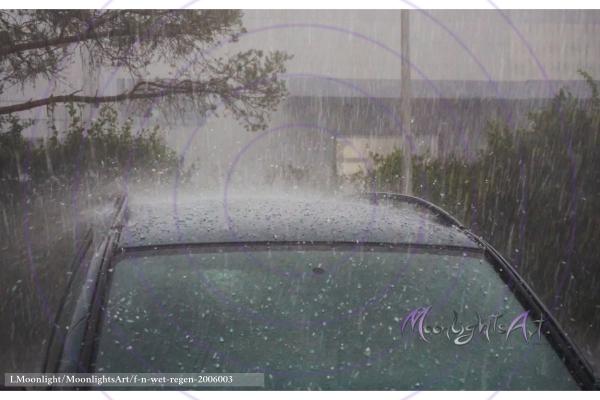 Starker Wolkenbruch mit Regen und Hagel trifft ein Auto
