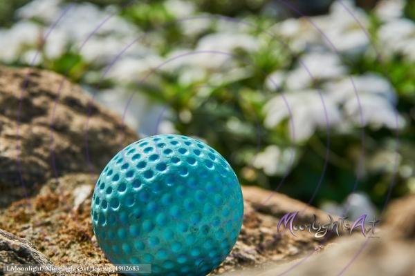Minigolf - Ball (Fokus) liegt vor Blumen